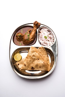 Курица колхапури тали - популярное индийское азиатское блюдо, состоящее из мяса птицы, яичного карри с чапати, риса, салата и сладкого гулаб джамун.