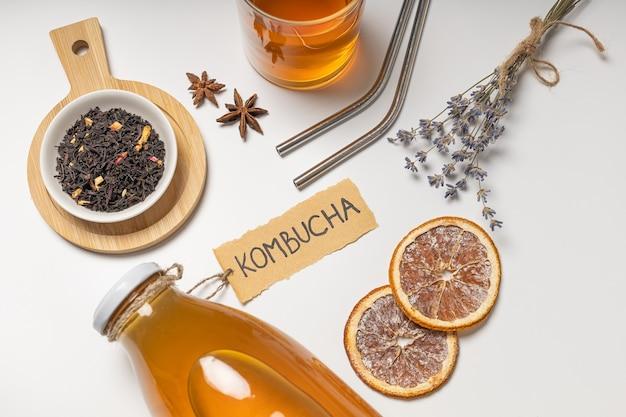 Бутылка чайного гриба с надписью «комбуча» и стакан напитка.