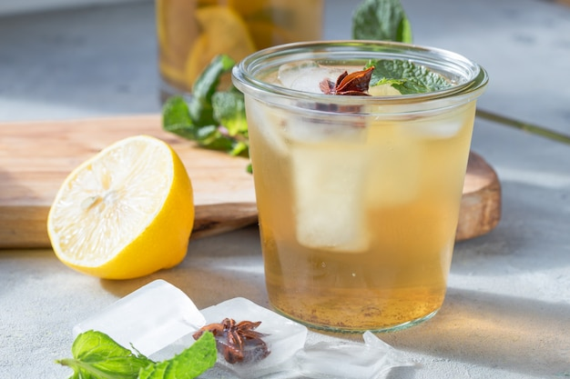 Kombucha or cider fermented drink in glass with anise ice. heathy probiotic drink