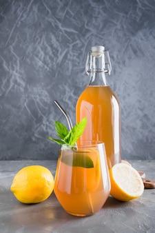 Kombucha healthy tasty drink in bottle and glass with lemon garnish mint.