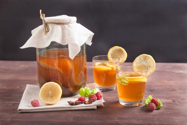 Чайный гриб в стеклянной банке, стакан с напитком и дольками лимона на деревянном столе. ферментированный напиток. концепция здорового питания.