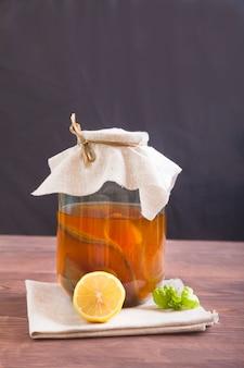 Комбуча в стеклянной банке, лимон и лист мяты на деревянном столе. ферментированный напиток. концепция здорового питания.