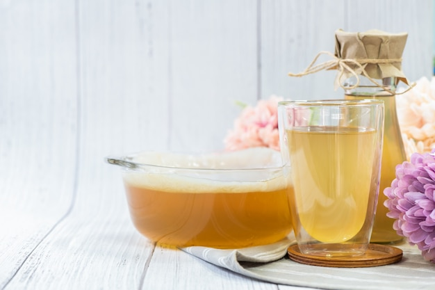 Чайный гриб в стакане на деревянном фоне, напиток из ферментированного сидра.