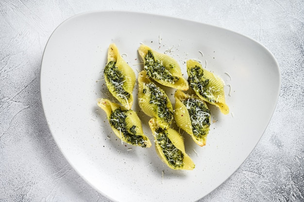 Konkiloni jumbo shells pasta conchiglioni stuffed with spinach on a plate on white table. top view.
