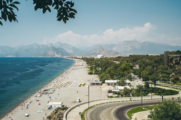 Пляж коньяалты в анталии, турция, длинный турецкий пляж на берегу средиземного моря теплым солнечным летом с ...