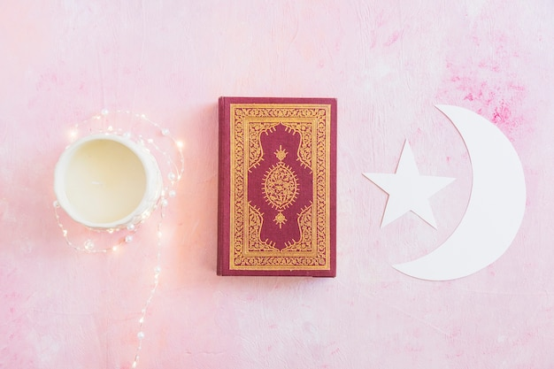 Koran book with crescent and candle