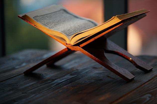 Исламская священная книга корана на деревянной подставке в традиционном мусульманском стиле с оранжевым солнечным светом и зеленым деревом размывает фон с копией пространства.