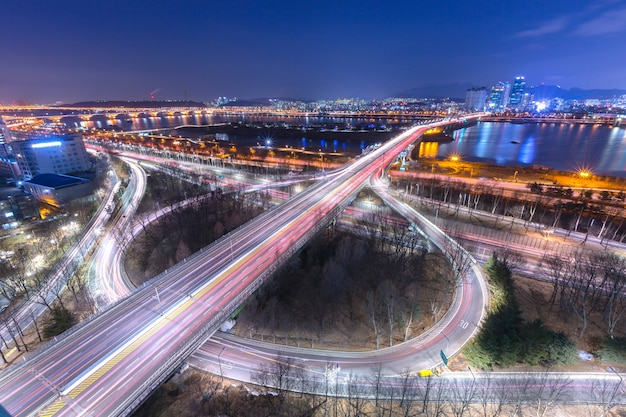 Korea travel, cars passing in intersection, han river and bridge at night in downtown seoul, south korea.
