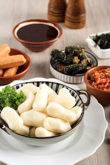 Рисовый торт «корейский батончик» с сыром моцарелла внутри. сырые ингредиенты для изготовления ттеокбокки, традиционной корейской кухни.