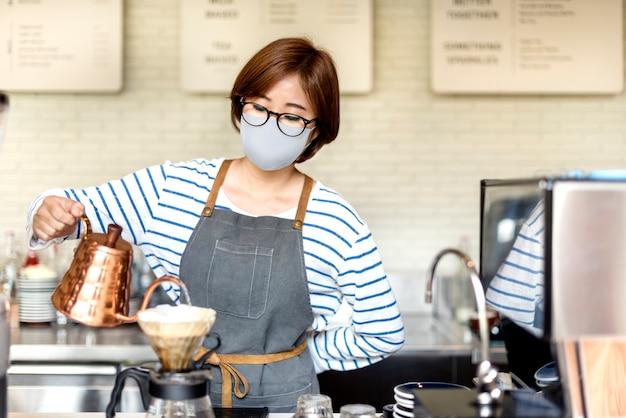 카페에서 드립 커피를 붓는 페이스 마스크의 한국 바리 스타