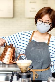 カフェでドリップコーヒーを注ぐフェイスマスクの韓国のバリスタ