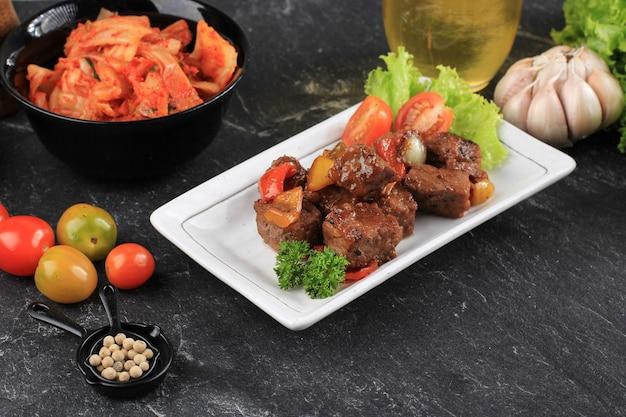 파프리카와 김치를 배경으로 한 한국식 흑후추 불고기. 흰색 접시, 검정색 배경에 제공됩니다. 와규 주사위 사이코로 쇠고기로 만든 불고기 마리네이드