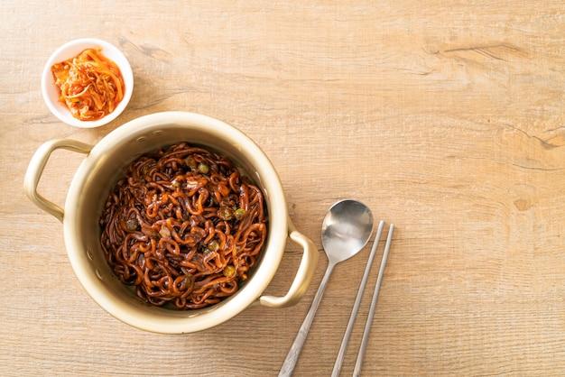 Черные корейские спагетти или лапша быстрого приготовления с обжаренным соевым соусом чачжунг (чапагетти). корейский стиль еды