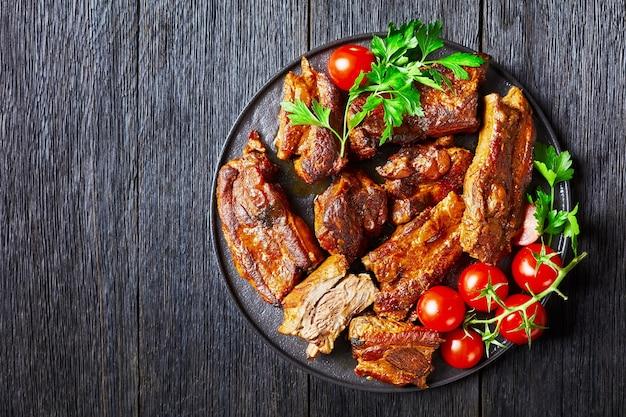 Свиные ребрышки, тушеные по-корейски, с хлопьями красного перца, помидорами черри и петрушкой на черной тарелке на темном деревянном столе, вид сверху, копия пространства