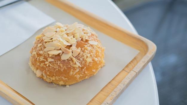 韓国のパンにんにく、カフェ環境の白いテーブルの木製プレートにアーモンドパン。