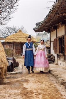 A korean couple in hanboks walking through a beautiful park