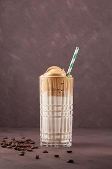 유리에 한국 음료 달고나 커피. 갈색 바탕에 인스턴트 커피의 거품과 차가운 우유. 세로 샷.