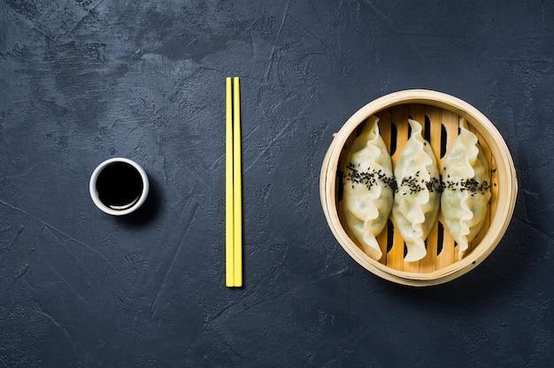 Korean dumplings in a traditional steamer, yellow chopsticks.