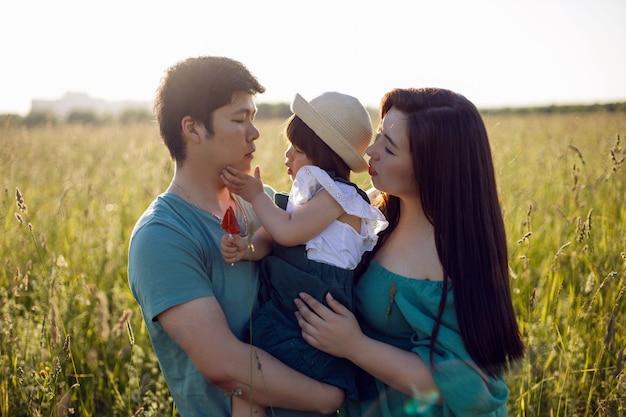 Корейская семья с дочерью идут в поле в траве на закате