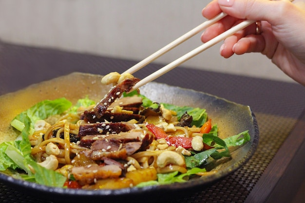 한국 음식. 한 소녀가 젓가락으로 고기, 견과류, 야채로 구성된 한국 요리를 먹습니다.