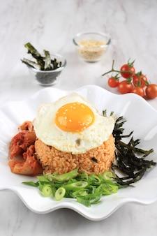 한국 음식: 볶음밥 또는 김치 볶음밥, 한국 전통 조리법 김치, 파, 참깨, 김을 곁들인 볶음밥, 써니 사이드 계란, 텍스트 복사 공간