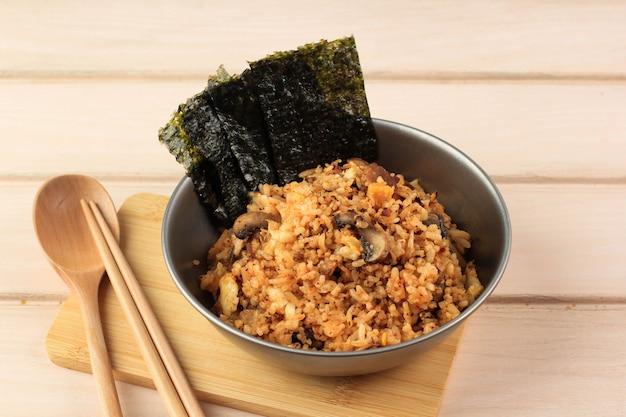 Корейская кухня: боккеумбап или жареный рис кимчи, традиционный рецепт южнокорейского жареного риса с кимчи, зеленым луком, семенами кунжута, грибами и нори (умывальник), место для копирования, вид сверху