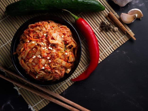한국 음식, 검은 접시에 양배추 김치가 어두운 배경에 설정되었습니다.