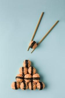 한국 음식 개념-참깨와 김을 곁들인 주먹밥, 밝은 파란색 배경에 간장, 젓가락 제공. 복사 공간이있는 상위 뷰. 수직 방향.