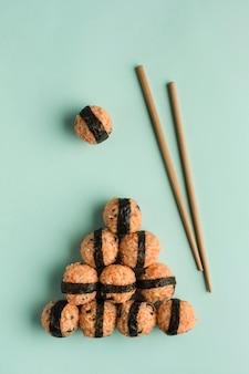 한국 음식 개념-참깨와 김을 곁들인 주먹밥, 밝은 녹색 배경에 간장, 젓가락 제공. 복사 공간이있는 상위 뷰. 수직 방향.
