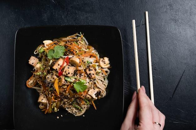 Корейская культура питания. женщина, использующая палочки для еды как традиционные столовые приборы