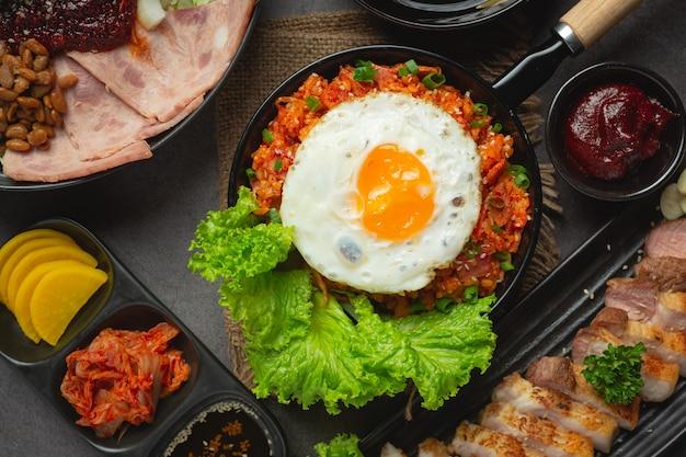 Корейская еда. жареный рис с кимчи подавать с жареным яйцом