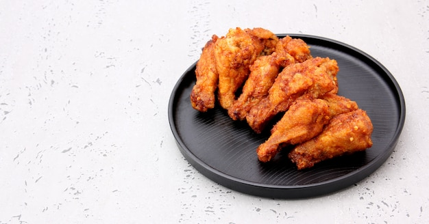 Korean fried chicken wings isolated on a gray background in studio.