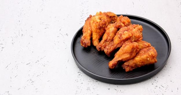 Корейские крылышки жареной курицы изолированные на серой предпосылке в студии.