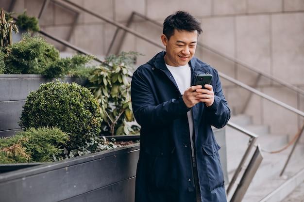 ツリーの外で電話を使用している韓国人の男