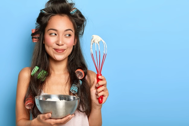 Korean housewife with hair curlers, busy cooking and preparing for birthday party, whisps cream with hand whisk
