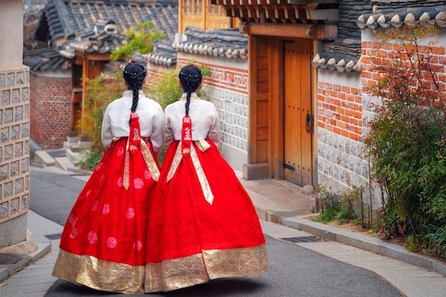 한복이나 한국의 한국 여성이 서울의 고대 도시에서 옷을 입고 걷다