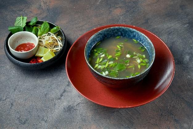 어두운 배경에 그릇에 쇠고기, 라임, 완두콩 콩나물, 고수를 넣은 한국 포보 수프. 아시아 음식