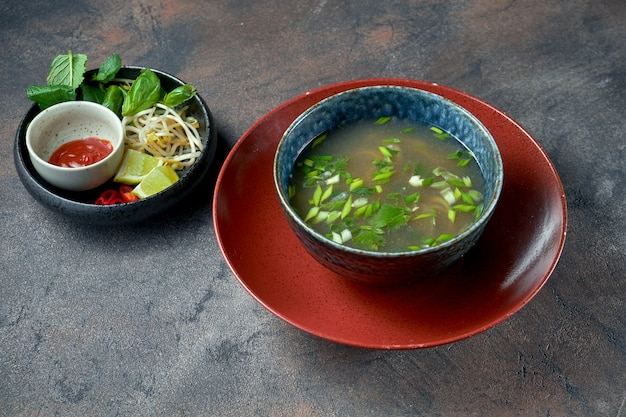 Korean pho bo soup with beef, lime, pea sprouts and cilantro in a bowl on a dark background. asian food