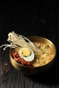 Корейский рамён в золотой миске, подавать с грибами симедзи, кимчи и полвареным яйцом на черном деревянном столе