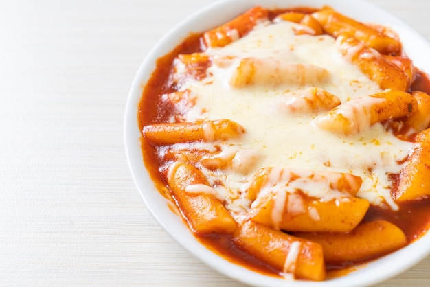スパイシーな韓国ソースとチーズの韓国ライスケーキ、チーズトッポッキ、トッポッキとチーズ-韓国料理のスタイル