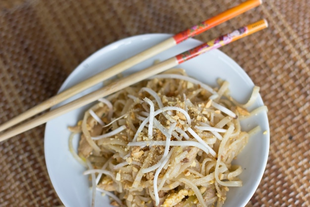 Korean rice noodles with soybean sprouts and crushed peanuts in a white bowl with chopsticks