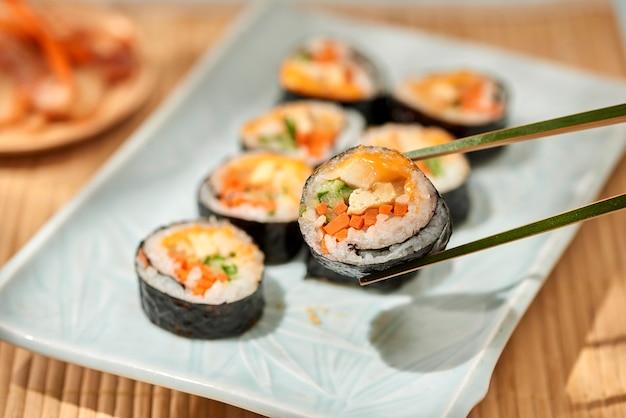 Корейский ролл кимбап (кимбоб) из вареного белого риса (бап) и различных других ингредиентов