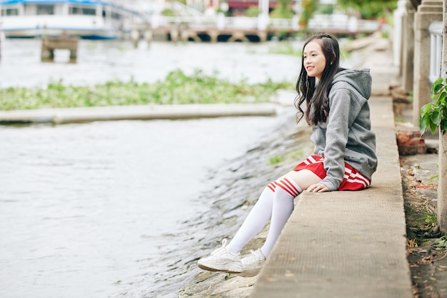 川岸に座って水を見ている制服を着た韓国の女子高生
