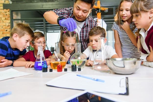 韓国の科学者は小学校の生徒に現代の実験室クラスで化学反応実験を示しています。