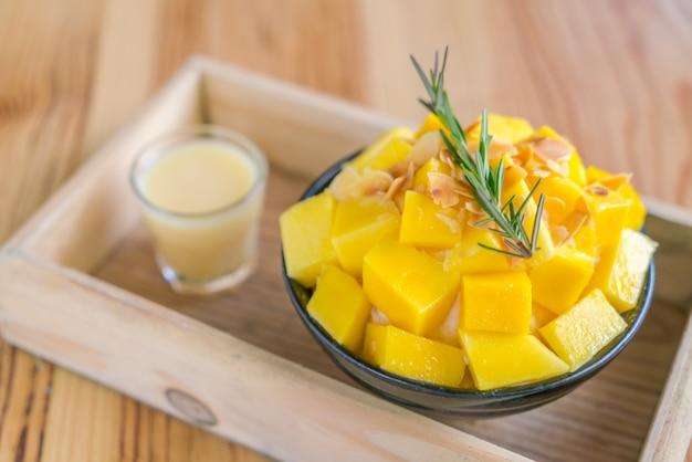 Korean style fresh mango shaved ice on wood table .
