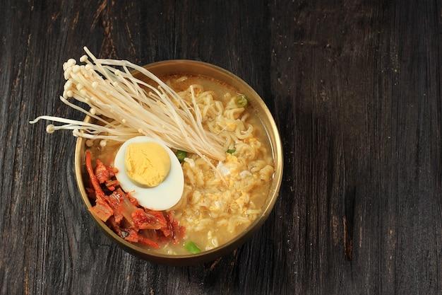 한국식 즉석 라면, 매운 맛을 낸 라면 또는 라면을 반숙 계란, 팽이버섯, 김치를 얹은 검은색 나무 탁자 위의 금색 한국 그릇에 담았습니다.