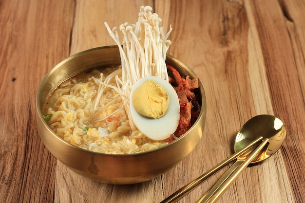 목탁 위 금색 그릇에 반숙 계란, 팽이버섯, 김치를 얹은 한국식 즉석 라면, 매운맛 라면 또는 라면. 텍스트를 위한 공간 복사