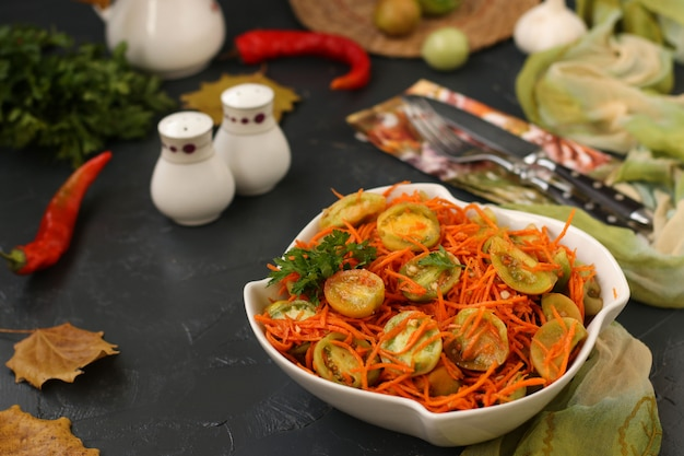 Korean-style salad with green tomatoes and carrots in a white salad bowl on dark