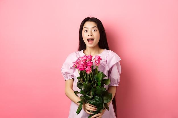 バレンタインデーにロマンチックなデートをし、バラの花束を持って、カメラに驚いて見えるドレスを着た韓国の十代の少女は、恋人、ピンクの背景からデートの贈り物を受け取ります。