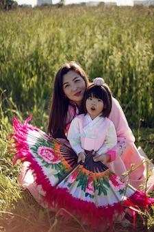 Кореянка в национальном костюме танцует фан-танец на поле с травой